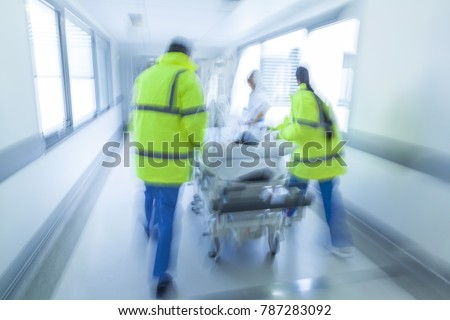 A motion blurred photograph of a child patient on stretcher or gurney being pushed at speed through a hospital corridor by doctors, paramedics and nurses to an accident and emergency room #787283092