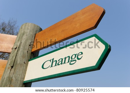 A motivational green and white wooden signpost pointing towards change  on sunny blue sky