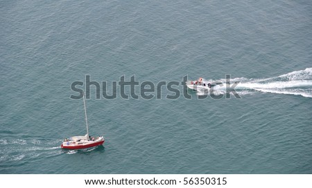 A motor boat and a sail boat passing eachother on open sea.