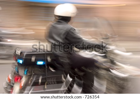 A motorcycle cop speeds by in hot pursuit of a car.  The long shutter speed is intentional, and conveys motion and action.
