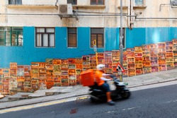 A motorcycle courier passing by the famous Graham Street Wall Mural, a colorful street art and a popular Instagram check-in spot in Central District, Hong Kong, China, Asia