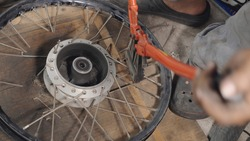 A motorcycle mechanic man using iron nippers. Cut the spokes from the wheels alignment. For weaving new steel spokes