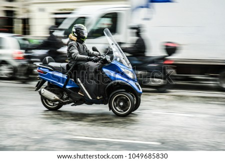 A motorcycle on road in big city. Motorbike or scooter on three wheels on road in motion. #1049685830