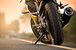 A motorcycle parking on the road right side and sunset, select focusing