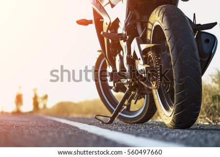 A motorcycle parking on the road right side and sunset, select focusing background. - Shutterstock ID 560497660
