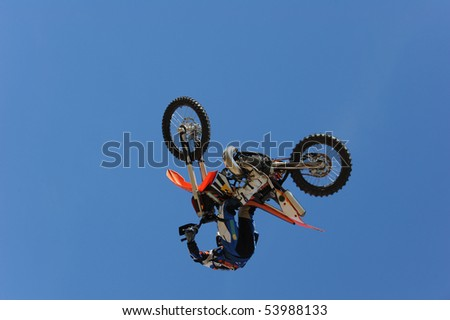 A motorcycle rider getting air while doing a stunt.