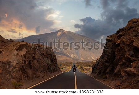 A motorcyclist has passed through a gorge and is driving on the straight and hilly road towards Mount Teide on the island of Tenerife. It is just before sunset in the evening. Stockfoto ©