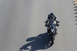 A motorcyclist in a helmet with a closed face rides on the road.