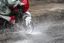 A motorcyclist rides along a flooded street