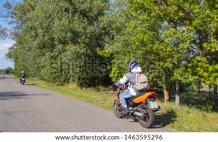 A motorcyclist rides on a highway at high speed, resisting the wind, goes on vacation in a joyful mood, overcomes the route laid by lovers of tourism and recreation on a two-wheeled vehicle. #1463595296