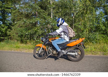 A motorcyclist rides on a highway at high speed, resisting the wind, goes on vacation in a joyful mood, overcomes the route laid by lovers of tourism and recreation on a two-wheeled vehicle. #1466762339