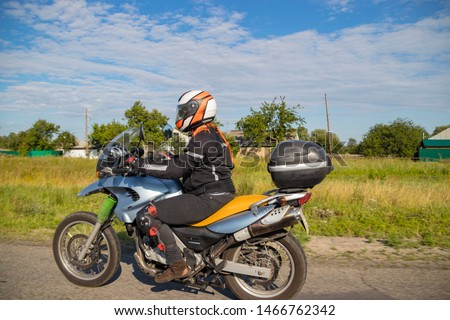 A motorcyclist rides on a highway at high speed, resisting the wind, goes on vacation in a joyful mood, overcomes the route laid by lovers of tourism and recreation on a two-wheeled vehicle. #1466762342