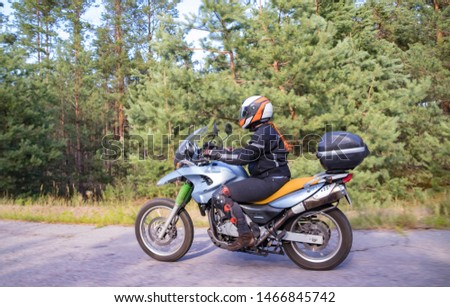 A motorcyclist rides on a highway at high speed, resisting the wind, goes on vacation in a joyful mood, overcomes the route laid by lovers of tourism and recreation on a two-wheeled vehicle. #1466845742