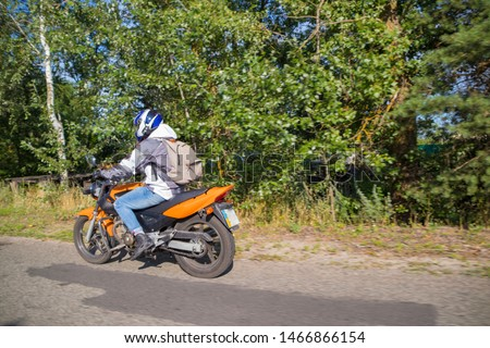 A motorcyclist rides on a highway at high speed, resisting the wind, goes on vacation in a joyful mood, overcomes the route laid by lovers of tourism and recreation on a two-wheeled vehicle. #1466866154