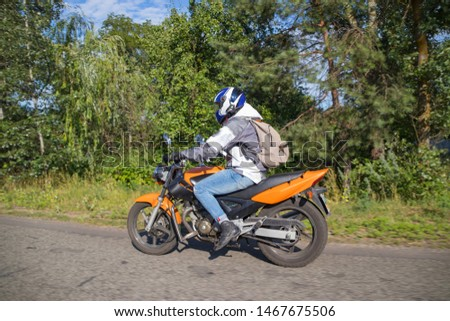 A motorcyclist rides on a highway at high speed, resisting the wind, goes on vacation in a joyful mood, overcomes the route laid by lovers of tourism and recreation on a two-wheeled vehicle. #1467675506
