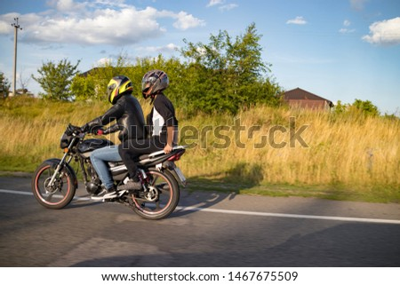A motorcyclist rides on a highway at high speed, resisting the wind, goes on vacation in a joyful mood, overcomes the route laid by lovers of tourism and recreation on a two-wheeled vehicle. #1467675509