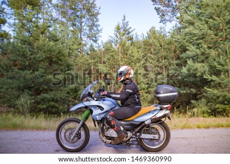 A motorcyclist rides on a highway at high speed, resisting the wind, goes on vacation in a joyful mood, overcomes the route laid by lovers of tourism and recreation on a two-wheeled vehicle. #1469360990