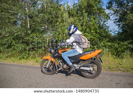 A motorcyclist rides on a highway at high speed, resisting the wind, goes on vacation in a joyful mood, overcomes the route laid by lovers of tourism and recreation on a two-wheeled vehicle. #1480904735