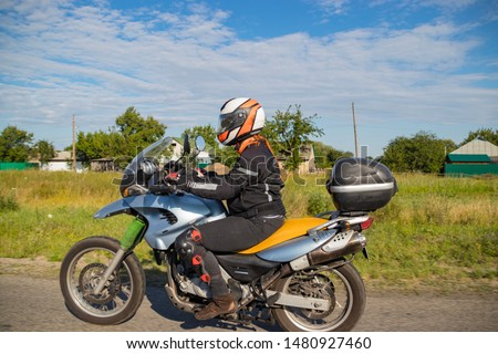 A motorcyclist rides on a highway at high speed, resisting the wind, goes on vacation in a joyful mood, overcomes the route laid by lovers of tourism and recreation on a two-wheeled vehicle. #1480927460