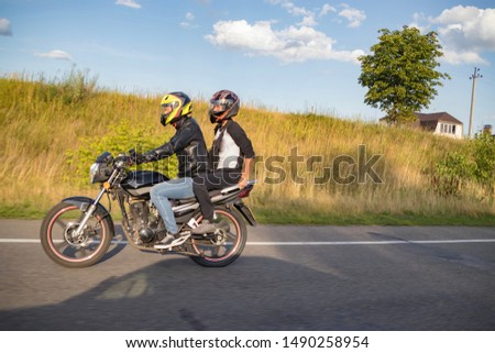 A motorcyclist rides on a highway at high speed, resisting the wind, goes on vacation in a joyful mood, overcomes the route laid by lovers of tourism and recreation on a two-wheeled vehicle. #1490258954