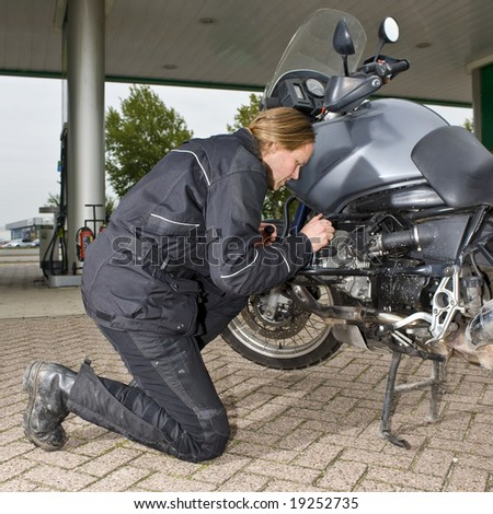 A motorist checking the oil level of his motorbike at a gas station