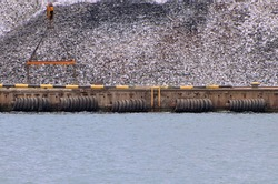 A mound of metal ingots on sea berth is prepared for loading onto a vessel
