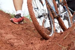 A mountain bike cyclist walking through a muddy road / Cycling in wet condition concept