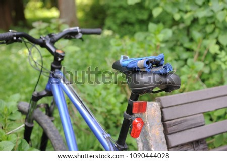 A mountain bike is parked at the park bench. Gloves for a cyclist lie on the bike seat. Concept of bicycle walks