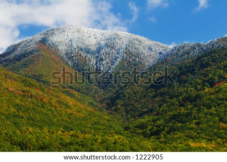 A mountain capped in snow, with autumn foilage at the lower elevations.  Smoky Mountains Nat. Park, USA. - stock photo