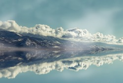 A mountain lined with clouds reflects in the adjacent lake, as a flock of birds fly above the water. A digital render from a photo I took of the mountains just after the season's first snow.
