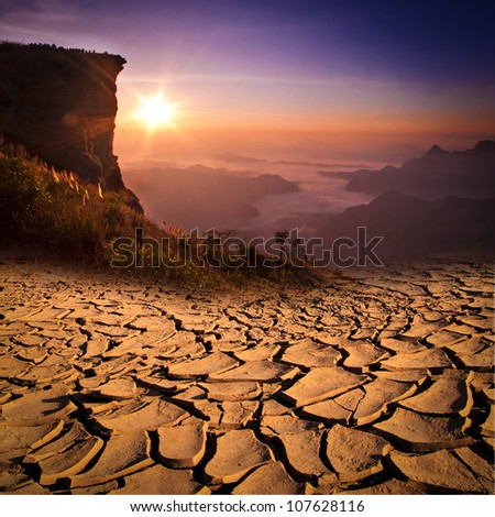 A mountain looks over a cracked earth landscape