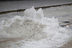 A mountain of snow on the street. Rainfall in the city in spring. Removing ice from asphalt. Large precipitation. Snow pile on the road. The parking lot is covered with snow.