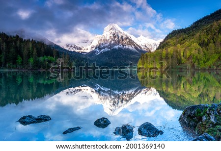 A mountain peak is reflected in a mountain lake. Mountain lake view. Lake in mountains. Mountain lake landscape