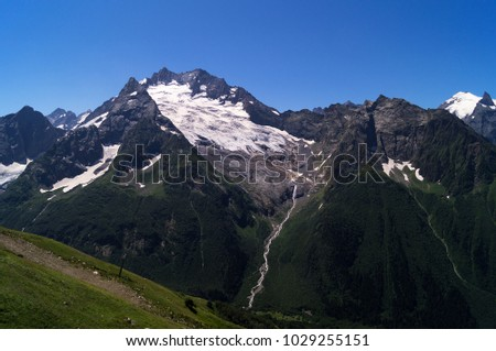 A mountain range with the lower slopes covered by a green forest and the remains of a melting glacier on rocky peaks, a cable car on the near slope. #1029255151