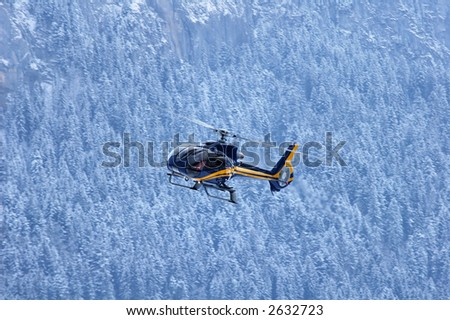 A mountain rescue helicopter coming in to land against a backdrop of snowy mountain forest.