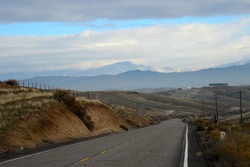 A mountain secondary road navigates the California foothills of the southern Sierra Nevada Range leading to a little snow at the higher elevations.