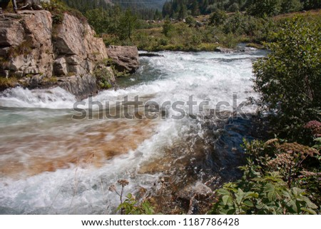 A mountain stream flows with its impetuous waters between the rocks #1187786428