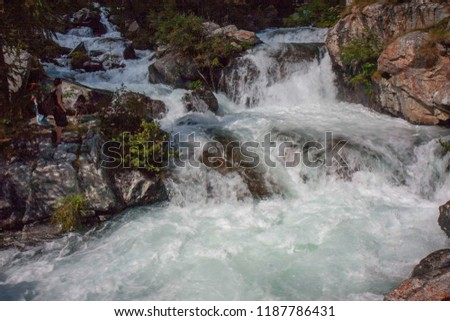 A mountain stream flows with its impetuous waters between the rocks #1187786431