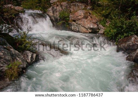 A mountain stream flows with its impetuous waters between the rocks #1187786437