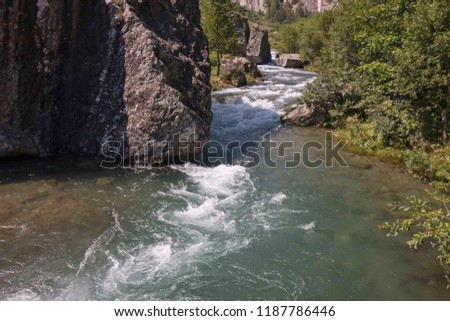 A mountain stream flows with its impetuous waters between the rocks #1187786446