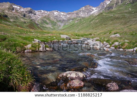 A mountain stream flows with its impetuous waters between the rocks #1188825217