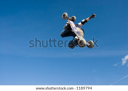 A mountainboarder in mid air with a deep blue sky in the background