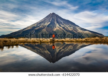 A mountaineer with an orange dress in a symmetric picture looking to the taranaki volcano in the north island of new zealand and with the reflection of tho mountain and the climber in a lake. Zeland