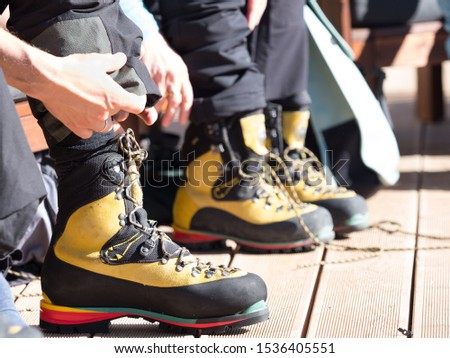 A mountaineering boot has been laced up and hands are folding trousers over them.A colourful striped sole is designed to take crampons.Image #1536405551