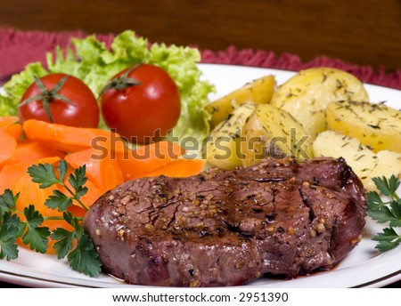 A mouth watering tenderloin steak with fresh vegetables and potatoes