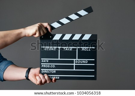 A movie production clapper board. Hands with a movie clapperboard on grey background with copy space, close-up.  #1034056318