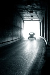 A moving car entering a dark tunnel in blur. Blurry image of a moving car.