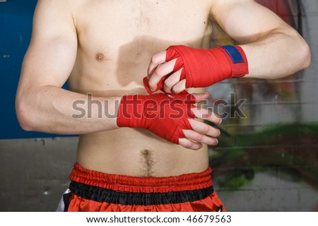 A muay thai fighter bandaging his hands before a fight
