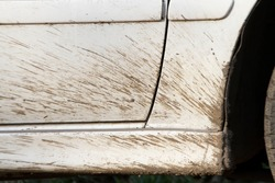 A mud splatter on a white car door and wheel arch.
