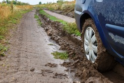 A muddy unpaved rural road and a car wheel in the mud.